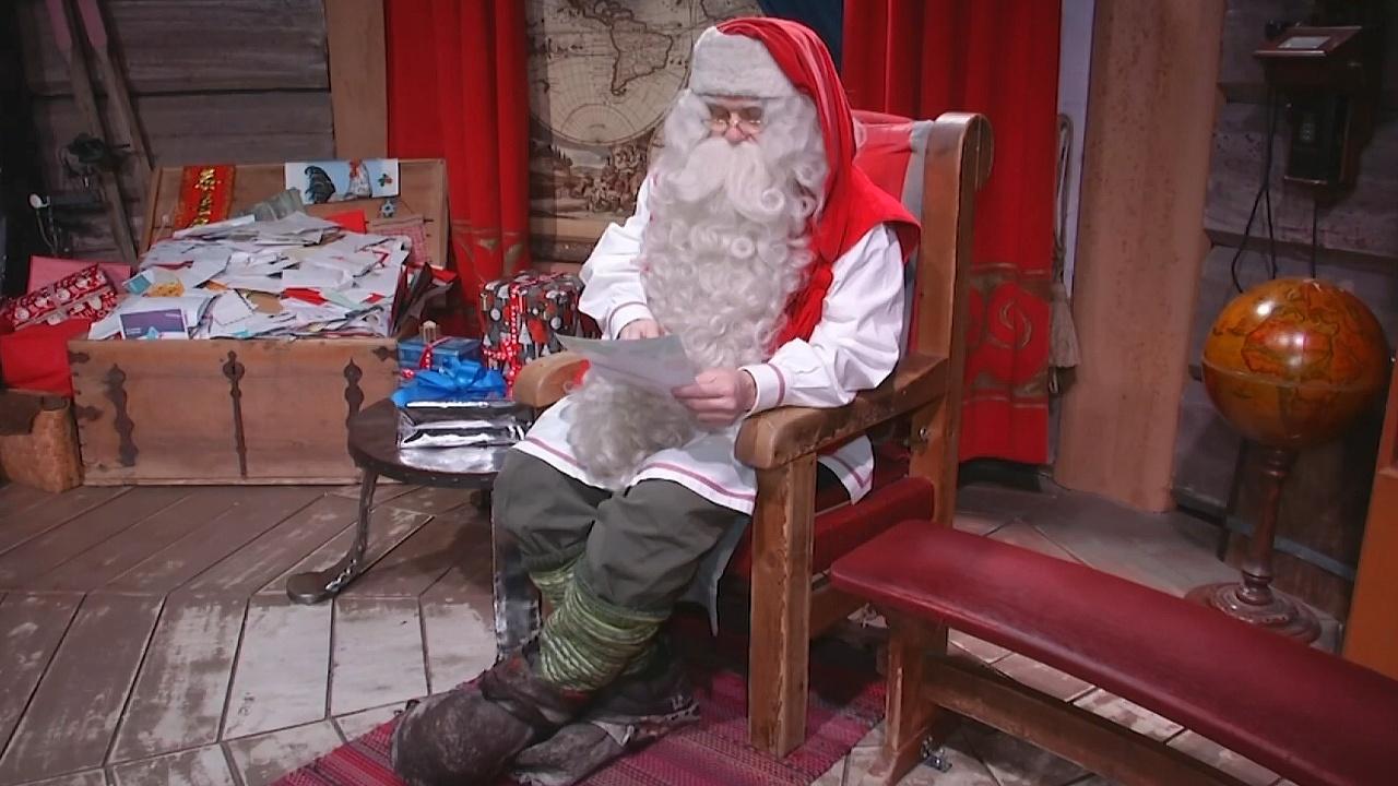 Санта-Клаус читает письма и готовит подарки к Рождеству