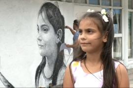 Кубинец пишет портреты детей на домах