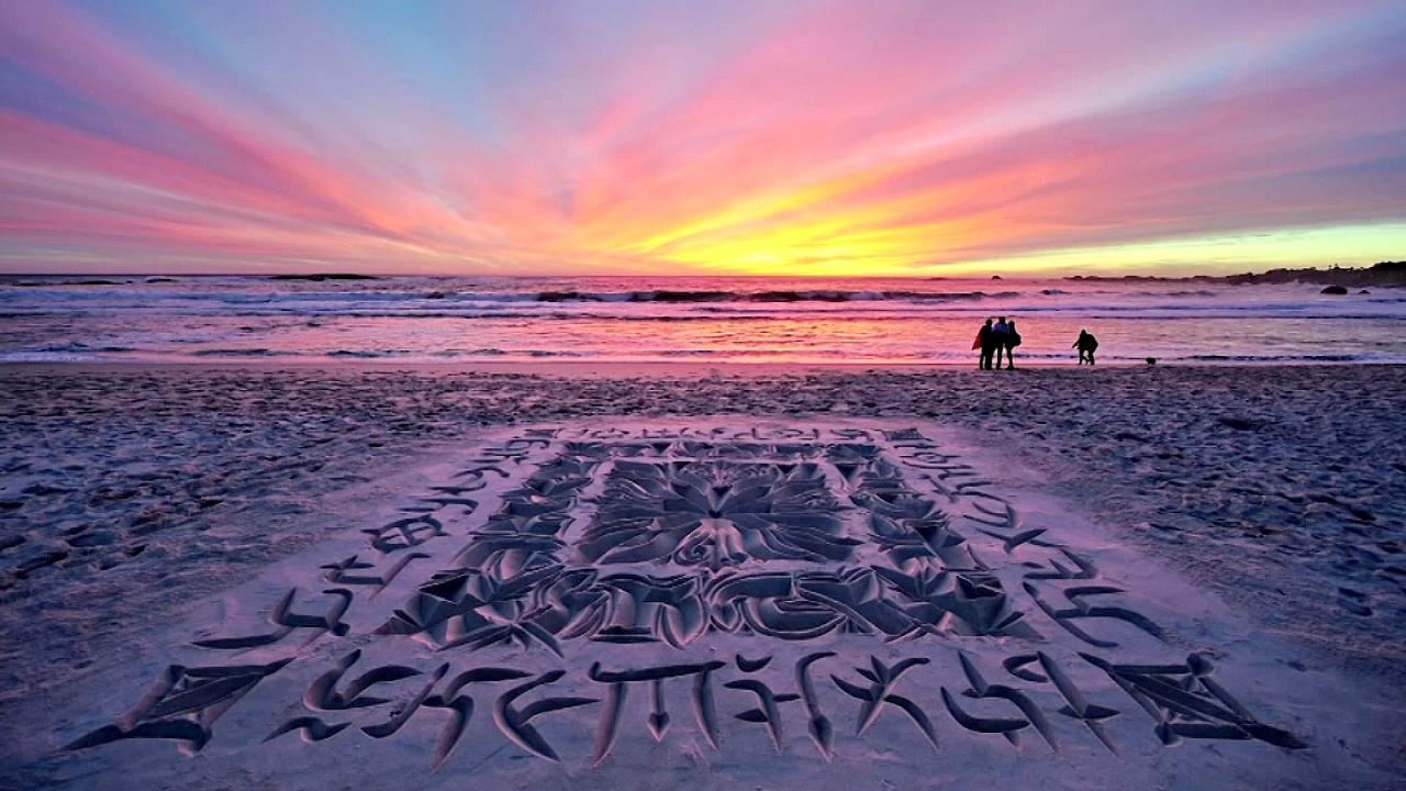 Каллиграфия на песке: художник создаёт узоры, которые смывают волны