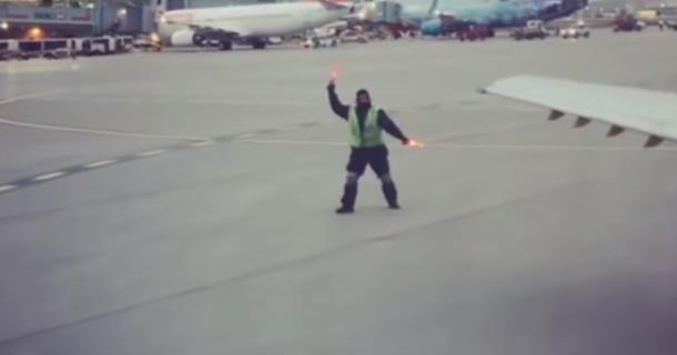 Работник авиакомпании танцует на взлётной полосе