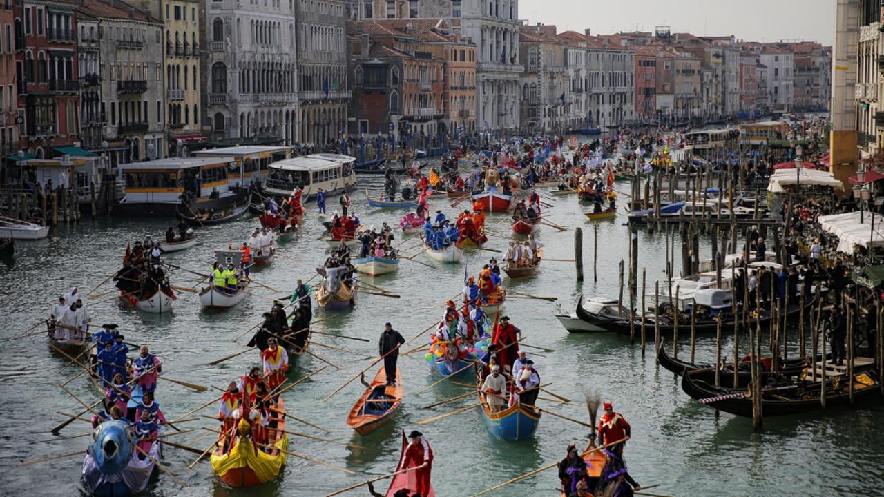 Венецианский карнавал: гондольеры в костюмах и туристы в масках