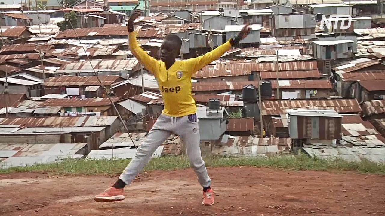 Кенийский школьник учится балету на улице на фоне трущоб