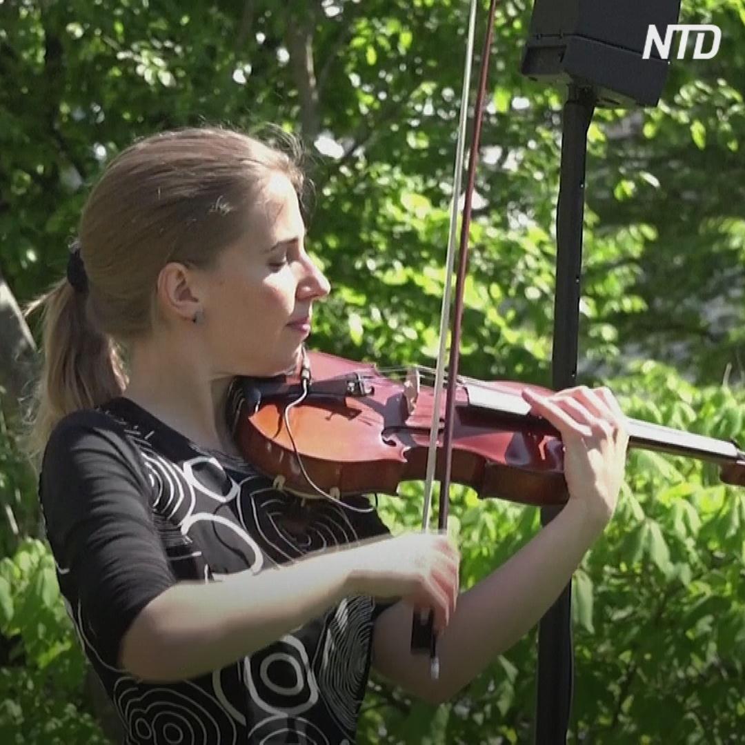 Швейцарская скрипачка исполняет музыку перед домом престарелых