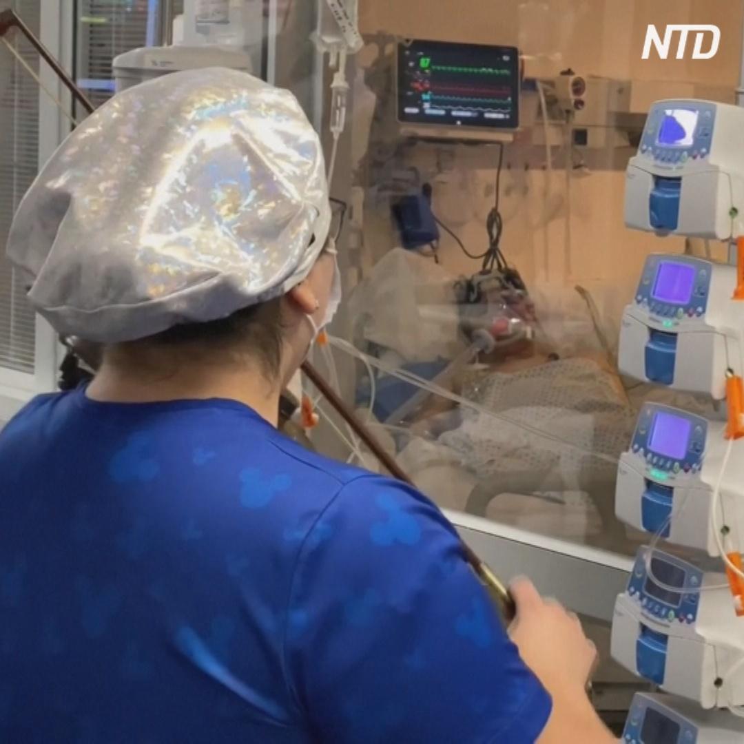 Медсестра играет на скрипке пациентам в коронавирусном отделении