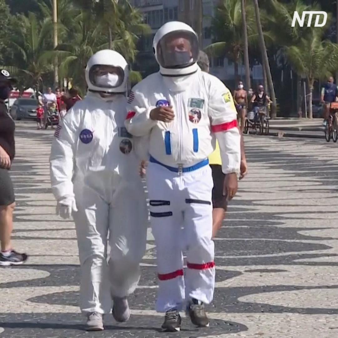 Бразильская пара ходит на пляж в костюмах астронавтов