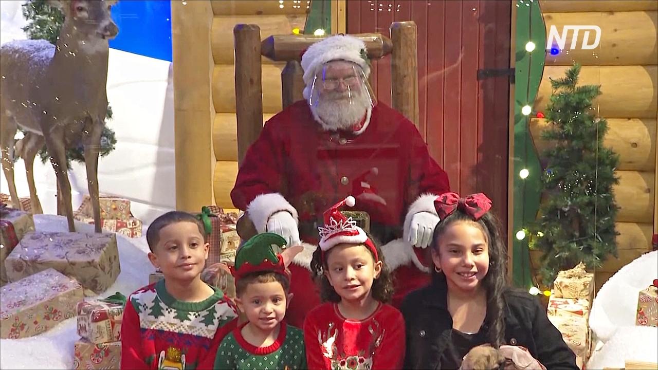 Посидеть на коленке не получится: Санта-Клаусы в США встречают детей за оргстеклом