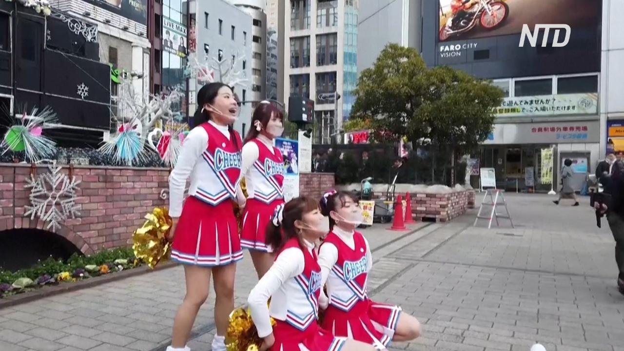 Чирлидеры танцуют у вокзала в Токио, чтобы подбодрить людей