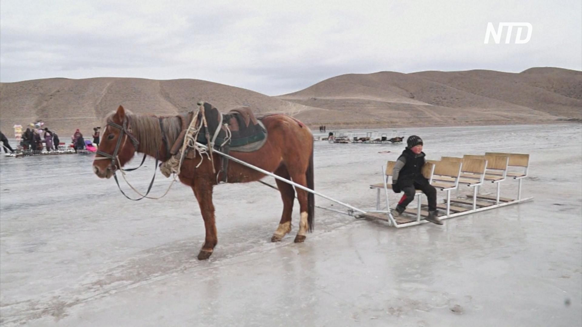 Кыргызские туристы катаются на самодельных санках по высокогорному озеру
