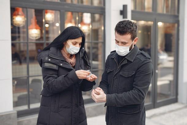 Молодая пара в медицинских масках дезинфицирует руки