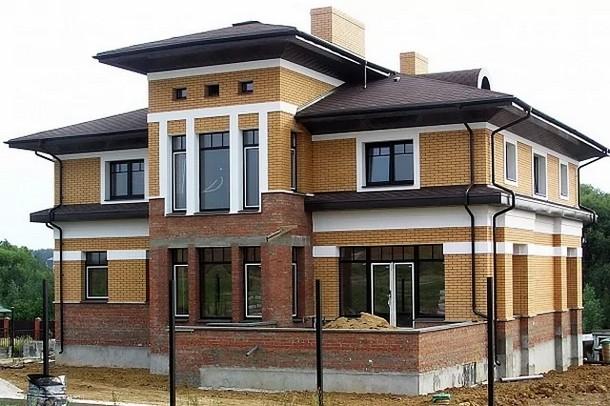 Дом из кирпича с ломаной крышей и панорамными окнами