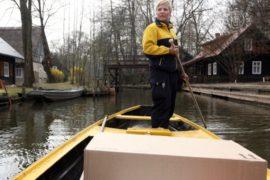 Женщина-почтальон доставляет письма по реке