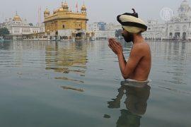 В Индии в честь праздника урожая окунаются в Ганг